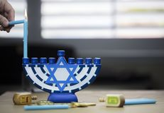Hanukkah candles lit for the holiday celebration surrounded by d. Traditional Hanukkah candles lit for the holiday celebration surrounded by dreidels and Stock Images