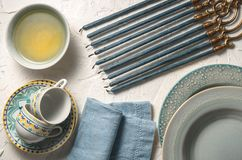 Hanukkah with candles, plates, butter in a bowl and blue napkin Royalty Free Stock Photos