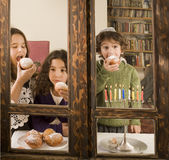 Hanukkah celebration. Children in front of a Hanukkia eating traditional jelly doughnut in Hanukka Royalty Free Stock Photo