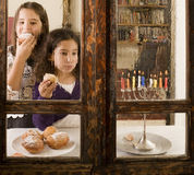 Hanukkah celebration. Children in front of a Hanukkia eating traditional jelly doughnut in Hanukka Royalty Free Stock Images