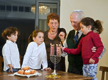 Hanukkah celebration. Grandparents and grandchildren lightening Menorah together Stock Images