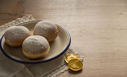 Hanukkah celebration concept-closeup of donuts and chocolate coi. Still life for jewish holiday Hanukkah with donuts and chocolate coins on White vintage