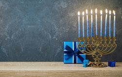 Hanukkah celebration with menorah. Gift box and dreidel on wooden table over blackboard background Stock Photos