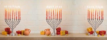Hanukkah background. Hanukkah celebration with menorah, gift box and dreidel on wooden table over brick wall background royalty free stock photos