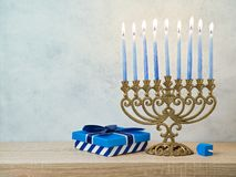 Hanukkah celebration with menorah. Gift box and dreidel on wooden table over bright background Stock Image