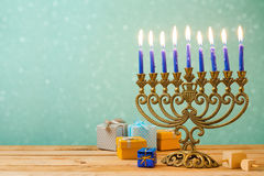 Hanukkah celebration with menorah on wooden table over bokeh background. Hanukkah holiday celebration with menorah on wooden table over bokeh background