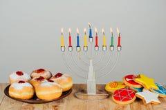 Hanukkah celebration. Traditional jewish menorah for hanukkah celebration, doughnuts and cookies on wooden table Royalty Free Stock Images