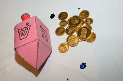 Hanukkah Crafts. A cardboard crafted dreidel and stickers along with chocolate money for hanukkah