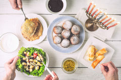 Hanukkah dinner with traditional dishes horizontal. Sufganiot , fried cheese , Hanukkah salad , latkes  with menorah and seasoning on the white wooden table top Stock Image