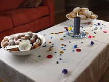 Hanukkah doughnuts and candle. On white tablecloth and various sweets consumed at this occasion Stock Photo