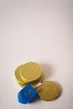 Hanukkah: Dreidel And Several Gelt Chocolate Coins Royalty Free Stock Images