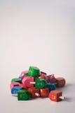 Hanukkah: Focus On Red Dreidel In Front Of Pile Of Toys. Colorful Hanukkah dreidels on white background
