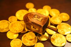Hanukkah gold gelt coins and dreidel on a table royalty free stock image