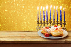 Hanukkah holiday sufganiyot with menorah on wooden table Royalty Free Stock Images
