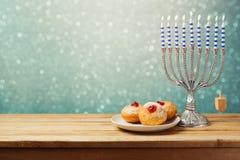 Hanukkah holiday sufganiyot and menorah on wooden table Stock Photos