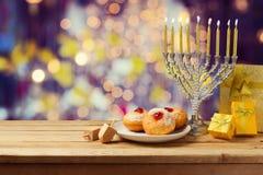 Hanukkah holiday sufganiyot and menorah on wooden table Royalty Free Stock Photos