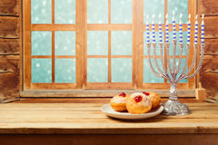 Hanukkah holiday sufganiyot with menorah on wooden table Royalty Free Stock Photos