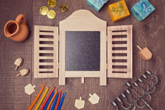 Hanukkah holiday symbols on wooden table with chalkboard. View from above Royalty Free Stock Images