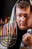 Hanukkah, a Jewish celebration. Candles burning in the menorah. The man in the background Stock Image