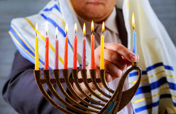 Hanukkah, a Jewish celebration. Candles burning in the menorah, man in the background. Royalty Free Stock Images