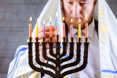 Hanukkah, a Jewish celebration. Candles burning in the menorah, man in the background. Stock Image