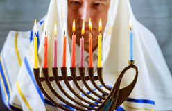 Hanukkah, a Jewish celebration. Candles burning in the menorah. The man in the background