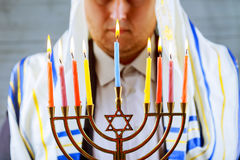 Hanukkah, a Jewish celebration. Candles burning in the menorah, man in the background. Royalty Free Stock Photos