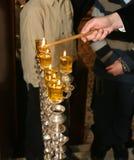Hanukkah, the Jewish holiday. Rabi lights a candle in the Jewish holiday of Hanukkah Royalty Free Stock Photography