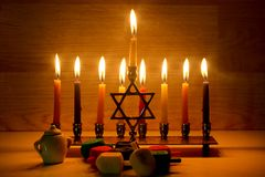Hanukkah is a Jewish holiday. Burning Chanukah candlestick with candles. Chanukiah Menorah. dreidel, savivon.  royalty free stock images