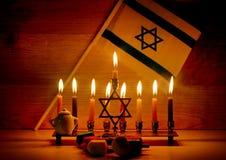 Hanukkah is a Jewish holiday. Burning Chanukah candlestick with candles. Chanukiah Menorah. dreidel, savivon. Flag of Israel.  royalty free stock photography