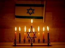 Hanukkah is a Jewish holiday. Burning Chanukah candlestick with candles. Chanukiah Menorah. Flag of Israel.  royalty free stock images