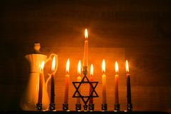 Hanukkah is a Jewish holiday. Burning Chanukah candlestick with candles. jug of oil. Chanukiah Menorah.  stock image
