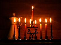 Hanukkah is a Jewish holiday. Burning Chanukah candlestick with candles. jug of oil. Chanukiah Menorah.  stock photo