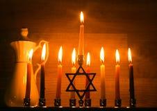 Hanukkah is a Jewish holiday. Burning Chanukah candlestick with candles. jug of oil. Chanukiah Menorah.  stock photography