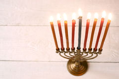 Hanukkah menorah with burning candles on the white wooden table horizontal Royalty Free Stock Photography
