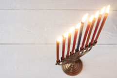 Hanukkah menorah with burning candles on the white wooden table Stock Photos