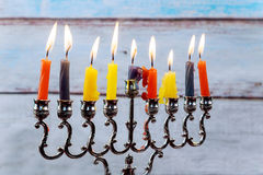 Hanukkah menorah with candles and silver dreidel. Royalty Free Stock Images