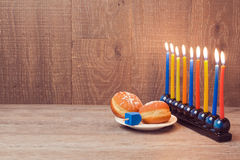 Hanukkah menorah with colorful candles and sufganioyt over wooden background Royalty Free Stock Photography