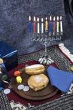 Hanukkah Menorah com velas, os presentes, o Dreidel e Jelly Fill iluminados foto de stock royalty free