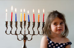 Hanukkah menorah. Cute Jewish girl look at fully lit Hanukkah menorah during the Jewish holiday of Hanukkah stock image