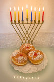 Hanukkah menorah and doughnuts. Hanukkah menorah with burning candles and traditional doughnuts Stock Photo