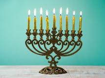 Hanukkah menorah. With golden candles on wooden table Stock Photos