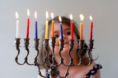 Hanukkah menorah. Happy Jewish girl look at fully lit Hanukkah menorah during the Jewish holiday of Hanukkah