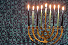 Hanukkah Menorah Lit Candles with blue fabric pattern background royalty free stock image