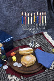 Hanukkah Menorah with lit Candles, Gifts, Dreidel and Jelly Fill. Hanukkah Menorah with lit Candles, Gifts, Dreidels and Jelly Filled Pastries served on a wooden royalty free stock photo