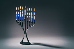 Hanukkah Menorah With Lit Candles. A silver Hanukkah menorah with lit blue and white candles