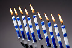 Hanukkah Menorah With Lit Candles. A silver Hanukkah menorah with lit blue and white candles royalty free stock photography