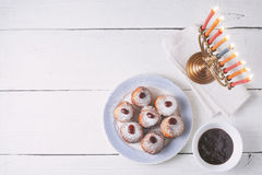 Hanukkah menorah and sufganiot on the white  wooden table top view Royalty Free Stock Photo