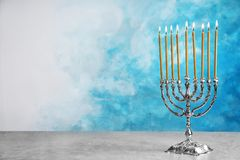 Hanukkah menorah on table. Against color background stock photography