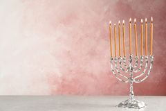 Hanukkah menorah on table. Against color background royalty free stock image